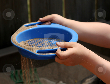 Sieving Sand stock photo, A childs hand sieving sand with a sieve. by Chris Hill