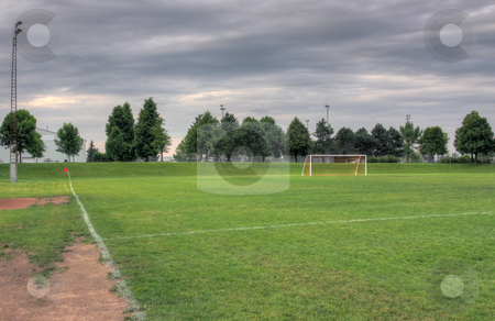 Grey Clouds and Soccer Field stock photo, A cloudy unoccupied soccer field with trees in the background. (HDR photograph)  by Chris Hill