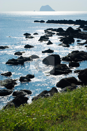 Rocky seashore with sun light reflection  stock photo, Rocky seashore with sun light reflect by the sea in the morning by Lawren