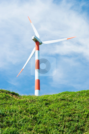 Wind turbine in green hill stock photo, clean energy concept.  wind turbine in green hill under cloudy blue sky.  by Lawren