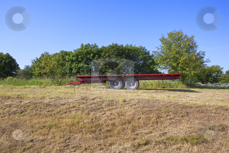 Red trailer stock photo, a red trailer in a newly cut hay field with a background of trees under a clear blue sky by Mike Smith
