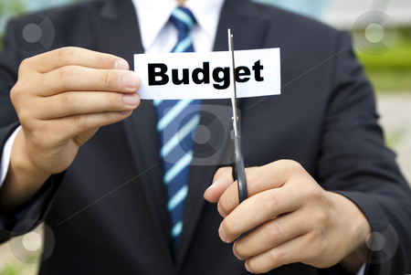 Businessman with scissors cutting label Budget stock photo, businessman with scissors cutting label Budget by tomwang