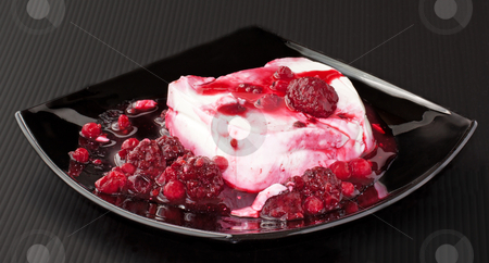 Panna cotta stock photo, Slice of panna cotta with red fruits over a black plate by Fabio Alcini