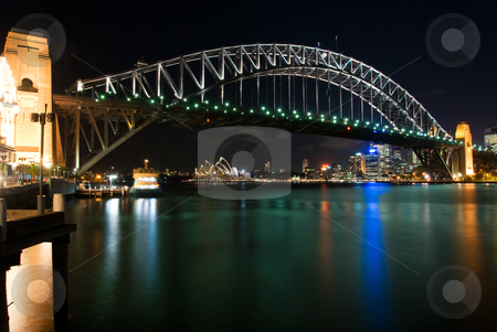 Sydney Harbour Bridge By Night stock photo, Sydney Harbour Bridge By Night with sparkling water reflection. The Sydney Opera House is at the background. by mroz
