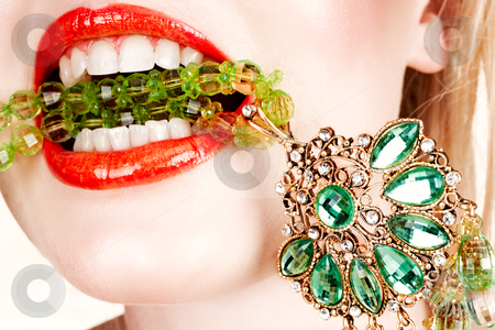 Woman lips with necklace stock photo, woman with bright red lips biting on emerald green expensive necklace with her teeth by lubavnel