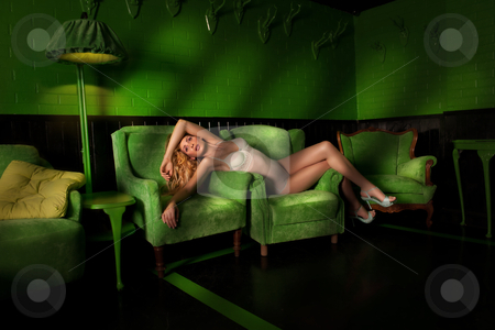 Beautiful, sexy woman in a dark, green room stock photo, On the chair in a room filled with night shadows by olgagoralewicz