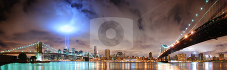 New York City stock photo, Remember September 11. New York City Manhattan panorama view with Brooklyn Bridge and Manhattan Bridge at night with office building skyscrapers skyline illuminated over Hudson River and two light beam in memory of September 11. by rabbit75_cut
