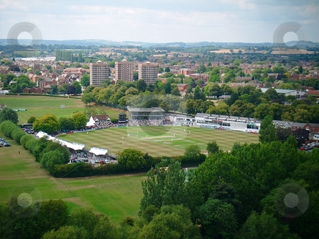 Cricket from above stock photo, Worcestershire county cricket club's New Road ground as viewed from the cathedral tower.  A match is in progress and the tower blocks int he distance appear to be watching it. by SallyM1976