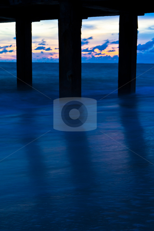 Pillars of the bridge on the beach. At sunset. stock photo, Pillars of the bridge on the beach. At sunset. by Na8011seeiN