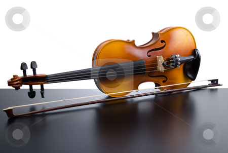 Violin stock photo, Violin on top of dark table partially isolated on white background. by Homydesign