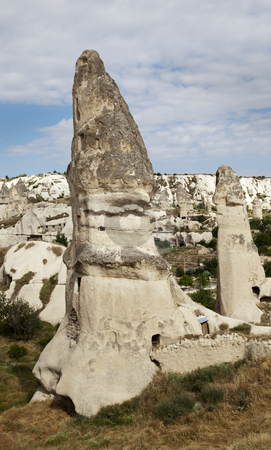 Fairy chimneys Goreme Cappadocia Turkey stock photo, Limestime weathered into fairy chimneys, Goreme, Cappadocia, Kapadokya, Turkey, portrait, copy space, crop area, blue cloudy sky, limestone cliff by Kantilal Patel