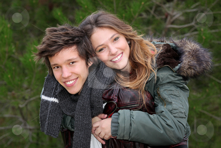 Happy smiling winter teen couple in piggy back stock photo, happy smiling teen couple in piggy back in winter clothing by mandygodbehear