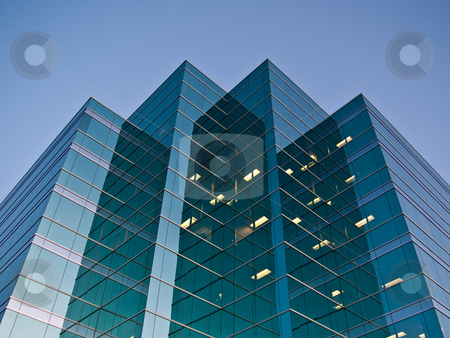 Modern Office Building at Dusk stock photo, Modern office building reflecting the setting sun with some interior lights visible. by Brian Guest