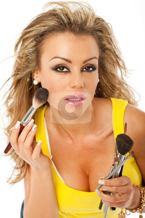 Woman brush makeup stock photo, beautiful woman is applying makeup with a brush by vilevi