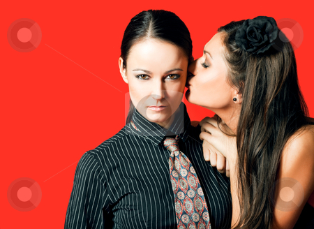 Girlfriends red stock photo, homosexual women couple, one kissing other on cheek, red background by vilevi