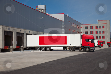Warehouse truck stock photo, Cargo trucks at an entrance of a warehouse by vilevi