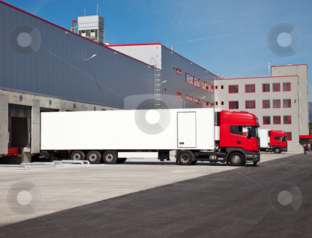 Truck warehouse logistic stock photo, cargo trucks at an entrance of a warehouse by vilevi
