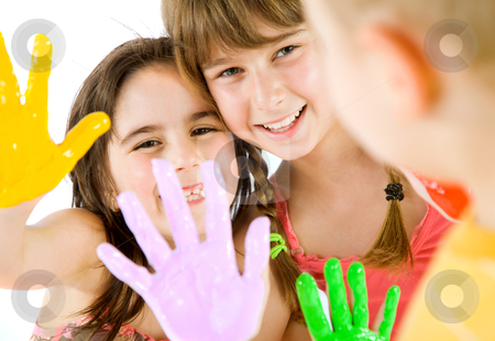 Children painted hands playing stock photo, Close-up of two little girls showing their painted colourful hands to a boy, focus on girls by vilevi