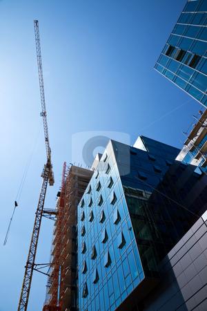 Construction office building stock photo, crane over a construction site of an office building by vilevi
