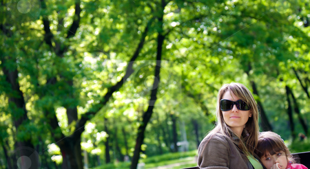 Mother daughter park stock photo, Mother with sunglasses sitting on bench in park embracing daughter by vilevi