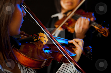 Female violinists stock photo, two violinists playing violins on a black background by vilevi
