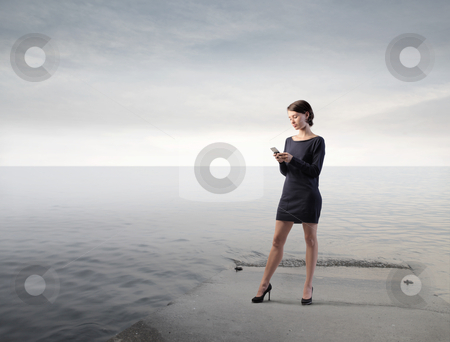Connection stock photo, Beautiful woman on a pier using a mobile phone by olly4