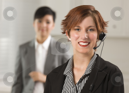 Pretty Red Haired Businesswoman with Headset in Office stock photo, Pretty Red Haired Businesswoman and Colleague with Headset in Office Setting. by Andy Dean