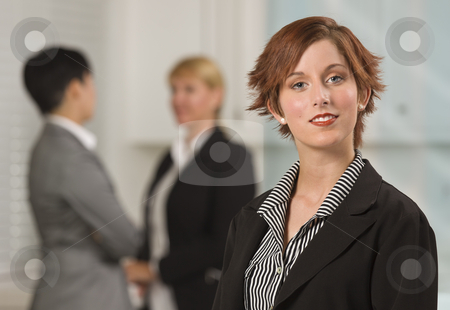 Pretty Red Haired Businesswoman with Colleagues Behind stock photo, Pretty Red Haired Businesswoman with Colleagues Behind in an Office Setting. by Andy Dean