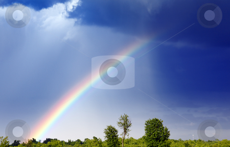 Rainbow stock photo, A rainbow forms as a storm passes through by macropixel