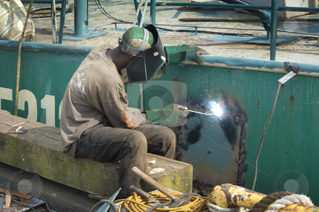 Welder stock photo, Welding a steel plate on the hull of a ship by Christian Delbert
