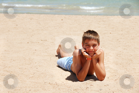Boy lying on the beach stock photo, caucasian boy lying on the sand beach in Egypt by Julija Sapic