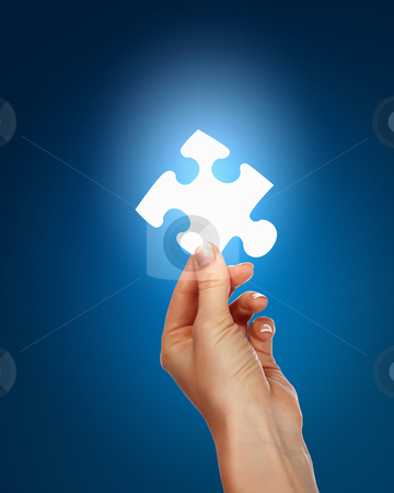 Human hand with a piece of puzzle stock photo, human hand with a blue shining piece of puzzle by Sergey Nivens