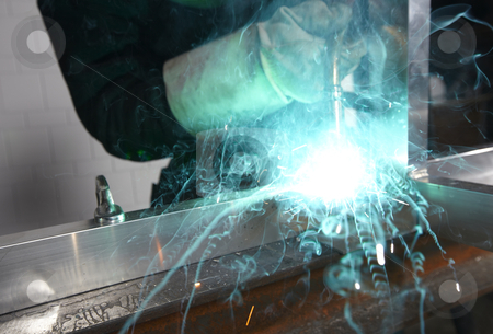 Welder with sparks stock photo, Welder with sparks arcing in a cyan light by sielemann