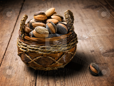 Almonds basket stock photo, Basket full of almonds on a grungy wooden background. by Sinisa Botas