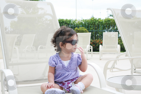 Adorable young baby girl wearing sunglasses in flirting position stock photo, adorable young baby girl wearing sunglasses in flirting position by dacasdo